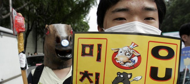 "South Korean protesters march during an anti-government rally against U.S beef imports Saturday in Seoul, South Korea. The sign reads ""Out, Mad Cow Disease."""