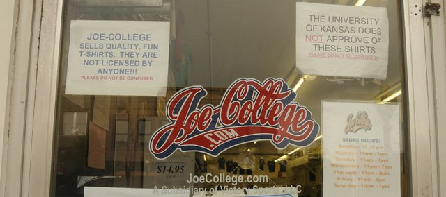 Signs are posted on the door of Joe-college.com to emphasize that the T-shirts are not licensed by Kansas Athletics Inc. Store owner Larry Sinks is headed to federal court to defend himself and his store from a suit by Kansas Athletics. The department wants Sinks to stop printing Kansas-related designs on blue T-shirts.