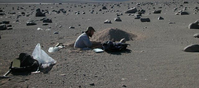U.S. Geological Survey researcher Jay Quade works in a test pit in Chile's Atacama desert, where bizarre microbes exist in this extreme climate. NASA's Phoenix lander is looking for conditions near Mars' north pole that could support primitive life similar to extreme life on Earth.