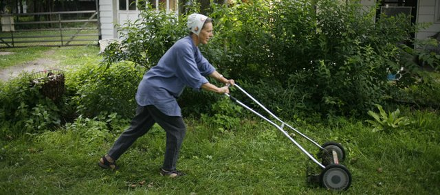 Natalya Lowther uses a manual reel mower to cut the grass at her home in North Lawrence in this June 2008 photo. Lowther grew up using a manual-style mower, and she said it's cheaper than a gasoline-powered mower and emits no pollutants.