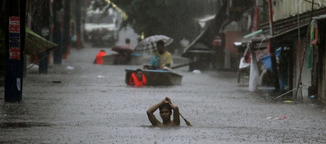 Residents wade through a flooded street in Manila, Philippines, following heavy rains brought by Typhoon Fengshen on Sunday. The typhoon lashed across the Philippines for a second day Sunday, killing at least 163 people as it submerged entire communities and capsized a passenger ferry carrying more than 740 passengers and crew.
