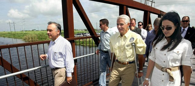 Robert Bucher, left, CEO of U.S. Sugar Corp., walks with Florida Gov. Charlie Crist and South Florida Water Management District Board Vice Chair Shannon Estenoz, right, as they arrive at a news conference Tuesday in rural Palm Beach County. They announced that U.S. Sugar Corp., the nation's largest producer of cane sugar, would go out of business in a $1.75 billion deal to sell its nearly 300 square miles of land to Florida for Everglades restoration.