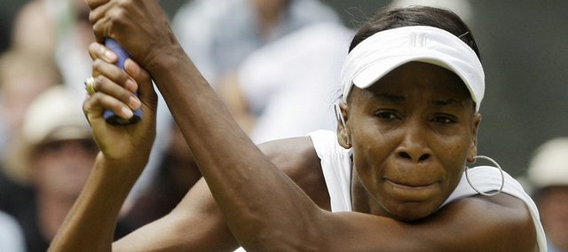 Defending champion Venus Williams returns a shot Tuesday during first-round action at Wimbledon.
