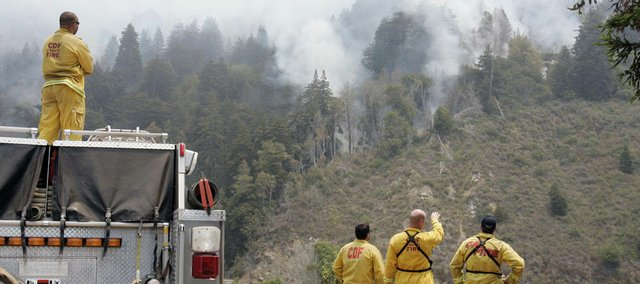 Firefighters watch a wildfire burn Tuesday in Big Sur, Calif. Last weekend's rare storm unleashed nearly 8,000 lightning strikes that set more than 800 wildfires across Northern California. The storm brought little or no rain.