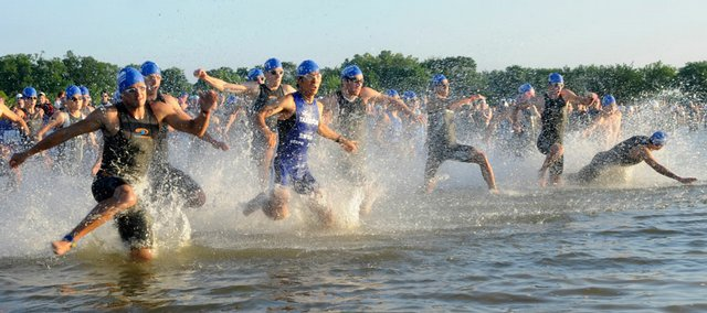 Triathletes hit the water at Clinton Lake at the start of the Ironman 70.3 Kansas. The event June 15 was cut short due to the threat of bad weather, making many of the competitors' times all but worthless.