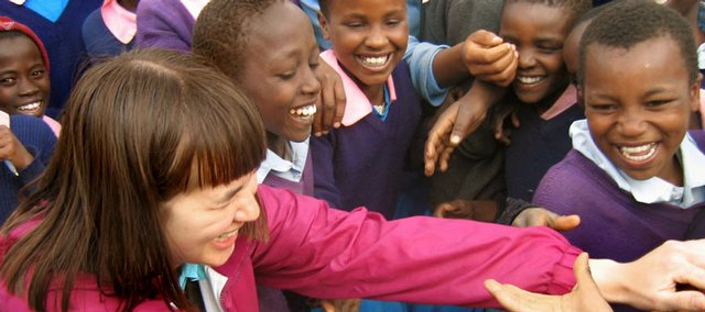 Shanxi Upsdell, left, greets schoolchildren May 30 at Kimbo Primary School in a rural area of Kenya, about 200 miles from Nairobi. The Lawrence-based organization Teach My Kenyan Children has a partnership with three Kenyan primary schools  - Ngurumo, Kambi and Thirikwa primary schools - and is considering a fourth partnership with Kimbo.