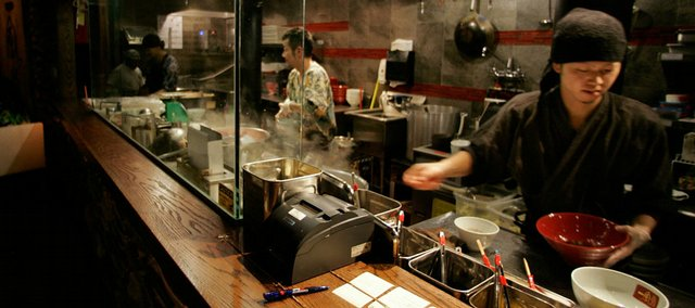 An order for a bowl of ramen noodles is filled, right, at Ippudo, a Japanese ramen noodle brasserie in New York.