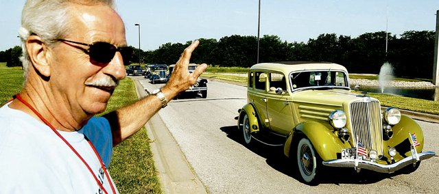 Don Smarker, a Hupmobile fan from Topeka, waves to drivers of some of the antique vehicles Tuesday that came to Lawrence for a tour of the city.