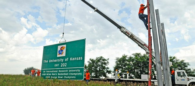 Workers from the Kansas Turnpike Authority erect a road sign announcing the exit for Kansas University two miles east of the East Lawrence exit on I-70. The new sign, which lays claim to Kansas' status as an international research university, 2008 NCAA Men's Basketball Champions and 2008 Orange Bowl Champions, was installed on Wednesday at mile marker 207.