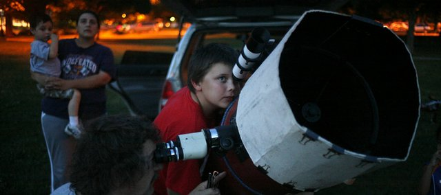 Rex Powell, bottom left, and Michael Heschmeyer, 11, center, both of Lawrence, try to get a bearing on Saturn with a telescope June 25 during an Astronomy Associates of Lawrence public viewing at South Park, 1200 Mass.