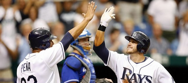 Tampa Bay's Carlos Pena, left, congratulates teammate Evan Longoria on his two-run home run in front of Kansas City catcher John Buck. Longoria's third-inning blast lifted the Rays to a 9-2 victory over the Royals on Sunday in St. Petersburg, Fla.