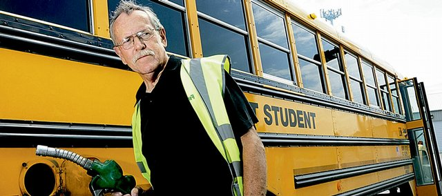 Jim Myers, bus driver for First Student Transportation, fills up a bus with diesel before picking up students for summer school recently. Skyrocketing gas prices have the school district dealing with new budget concerns.