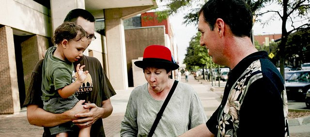 Jay Cady, right, and Leslie Cady, middle, both of Mission, show Oren Whalen, 2, and his father, Dan Carey-Whalen, both of Lawrence, a magic trick Wednesday at Ninth and Massachusetts streets before the Busker Fest planning committee's tour of downtown. The Busker Fest is set for Aug. 23 and 24 in Lawrence.