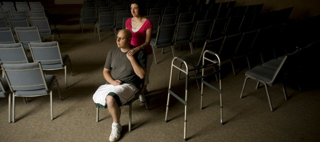 Brandon and Jody White are shown in the sanctuary of Heartland Community Church, 619 Vt., where Brandon works as the youth pastor. Brandon recently had his right leg removed because of bone cancer.