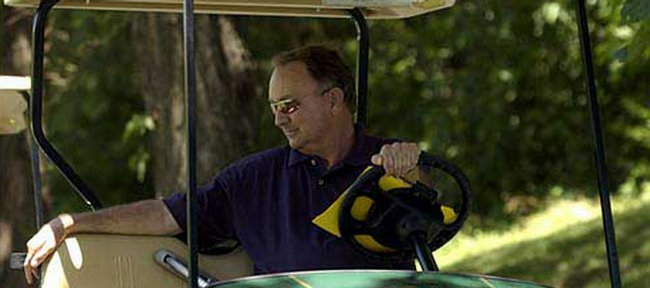 Kansas University golf coach Ross Randall watches the 2003 Be Like Bob Memorial at Alvamar from his golf cart in this file photo. After 30 years of service at KU, Randall retired on Tuesday.