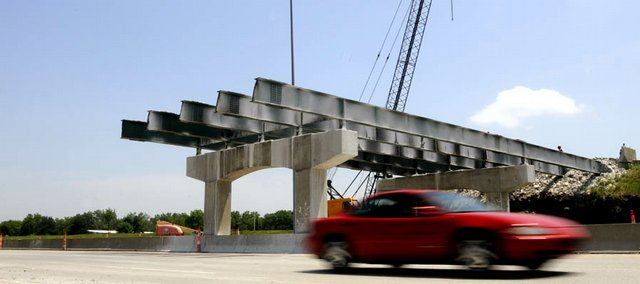 A car passes Thursday afternoon in the westbound lanes of the Kansas Turnpike at the West Lawrence interchange. Half of the overpass has been taken down.