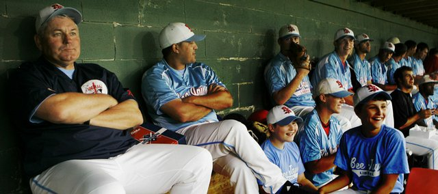 Liberal Bee Jays manager Mike Hargrove, left, and members of his team, wait in the dugout during a rain delay on July 2. He wrote Cal Ripken, Manny Ramirez and Ichiro Suzuki onto lineup cards during 16 years as a major league manager. For Mike and Sharon Hargrove, who are living in the basement of someone's home, things are decidedly different.