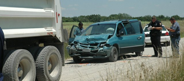 A Douglas County sheriff's deputry and a Baldwin City police officer investigate an accident south of Baldwin City that injured a Baldwin City woman about 1 p.m. Tuesday. The minivan was westbound on North 150 Road when it ran into the back of a dump truck. There were three other passengers in the minivan, including two small children who were in car seats and unharmed. The driver of the dump truck was not hurt.