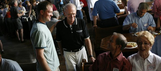 Don Gardner, center, known as Red Dog, catches up with friends Thursday during the Red Dog's Dog Days 25-year celebration at Abe and Jake's Landing, 8 E. Sixth St. Gardner started his summer fitness program with a small group of high school students 25 years ago. On his left is Jeff Hatfield, a 1987 Lawrence High School graduate, who was a student in Gardener's first Dog Days workout.