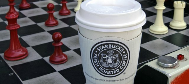 Men play chess over a cup of Starbucks coffee in a file photo from earlier this month in Alameda, Calif. Starbucks Corp. has announced which 600 company-operated U.S. stores it plans to close in the next year. The Lawrence store at 647 Mass. will remain open.