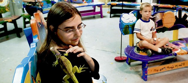 "Lawrence artist Jenny Lepley, 18, relaxes with her pet iguana ""Iggy"" on Friday on a bench she designed for the sixth-graders at Langston Hughes School after the Van Go Mobile Arts 10th annual ""Benchmark"" event. The 20 benches designed and crafted by 20 young artists were unveiled during the reception for family, friends and the local businesses that purchased them."
