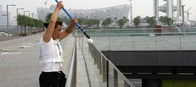 A Chinese woman cleans a glass barrier Friday near the iconic Bird's Nest National Stadium, background, in Beijing.