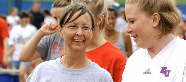 Nick Krug/Journal-World Photo.Beverly Gardner talks with workout leader Stephanie Temple as the two make their way to the north endzone of Memorial Stadium for running exercises Tuesday, July 8, 2008.