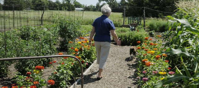 Linda Campbell walks the path into the flower and vegetable garden she shares with her husband, Win. In addition to the garden, the Campbells' home and yard southwest of Lawrence offer several shaded seating areas with scenic views.