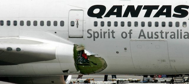 An airline mechanic walks past the damaged right wing fuselage of a Qantas Airways Boeing 747-400 passenger plane following an emergency landing at the Ninoy Aquino International Airport Friday in Manila, Philippines. The plane, with about 350 passengers and 19 crew,  was enroute to Australia from London when an explosion punched a hole in the right wing fuselage, passengers said.
