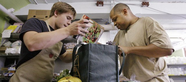 Saad Hopkins, right, entering the University of Washington as a junior in the fall, helps bag his groceries with volunteer Chris Tritt at the University District Food Bank on July 15 in Seattle. In the past year, the price of groceries has jumped nearly 5 percent and the costs of some staples such as milk and bread - the core of a college diet - have shot up by more than 30 percent. That's driving up demand at food banks and prompting some students to apply for food stamps.