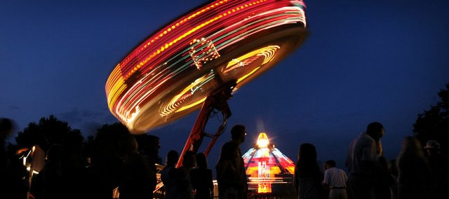 Douglas County fairgoers wait in line for carnival rides at the 2008 Douglas County Fair as the Zondar rises into the night sky. The fair got underway Saturday and will continue through the week.