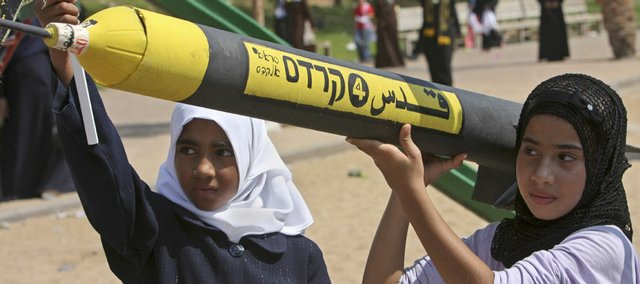 "Palestinian girls hold a homemade model of a rocket that reads ""Al-Quds,"" the Arabic word used for Jerusalem, in Hebrew and Arabic on it Wednesday during an Islamic Jihad rally in Gaza City. The rally was for children who are part of summer camps run by Islamic Jihad-funded organizations. Although Mideast peace talks continue, hope is waning for a signed deal before January."