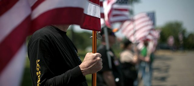 Veterans and volunteers hold U.S. flags during a June 14, 2008, memorial service in Bloomington for Minnesota National Guard soldiers who were killed in Iraq.