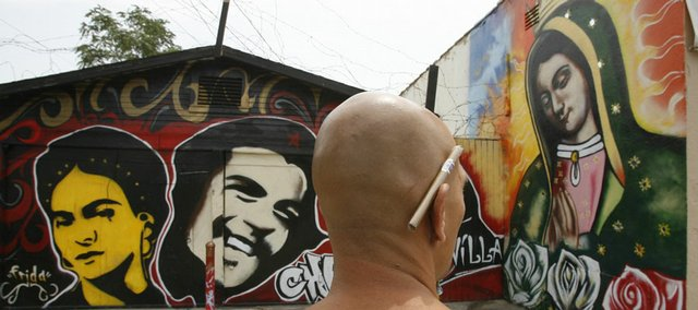 Graffiti artist George Curiel, 38, looks at his mural artwork last month in central Los Angeles. Once armed only with cans of spray paint, graffiti crews have taken up arms in recent years to protect their work.