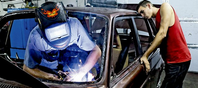 Ernest Hatch welds a dash bar onto a Volvo demolition derby car as his son, James Hatch, 20, oversees the work on Wednesday evening at 19th Street Auto Recyclers, 2005 E. 19th St. The father and son plan to collide with dozens of other drivers in tonight's Demolition Derby, which starts at 7:30 p.m. at the rodeo arena at the Douglas County 4-H Fairgrounds.