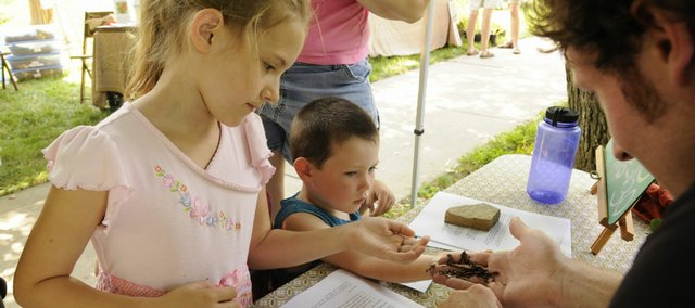Rose Naramore-Winfrey, 7, left, and her cousin, Utah Hester, 2, touch composting red worms held by Eric Williams, co-owner of The Green Worm, on Saturday at the Little Green Festival in South Park.  The Green Worm, which promotes sustainable living through the creation of natural, soil-enriching products for garden, lawn and house plants, was one of dozens of vendors that had tables at the green living event.