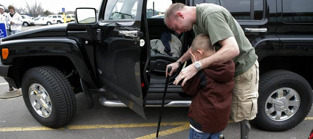 "Sgt. John Kriesel comforts his son, Broden, 5, outside a mall in Roseville, Minn. Kriesel lost both of his legs in a roadside bomb attack while patrolling near Fallujah, Iraq, in December 2006. Kriesel's story is one of many told in ""The Long Haul,"" a series about a Minnesota National Guard unit by Associated Press writer Sharon Cohen and featured at LJWorld.com."