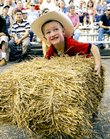 Colin Galiano, 3, heaves a 15-pound hay bale onto a platform during the 2008 hay bale throwing contest at the Douglas County 4-H Fairgrounds. The contest came before the demolition derby rally.