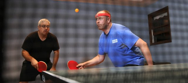 Table tennis players Terry Pentecost, left, watches as Jonathan Paretsky serves during a match Thursday. Paretsky built a custom room in his home that was painted, lit and designed specifically for playing table tennis.