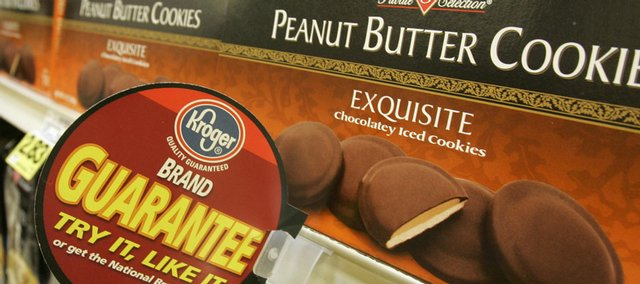 Kroger brand premium cookies are stocked on a shelf with a customer-satisfaction guarantee at a Kroger store last month in Cincinnati. As budgets get tighter and food gets more expensive, American shoppers are increasingly switching to store brands.