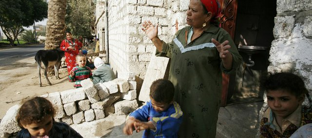 Harisa Mesed talks outside a home in the Upper Egyptian village of Sultan Zawyit as children from the village play on Dec. 5, 2007. Harisa  is one of several women in the village who are trying to convince their neighbors not to circumcise their daughters.