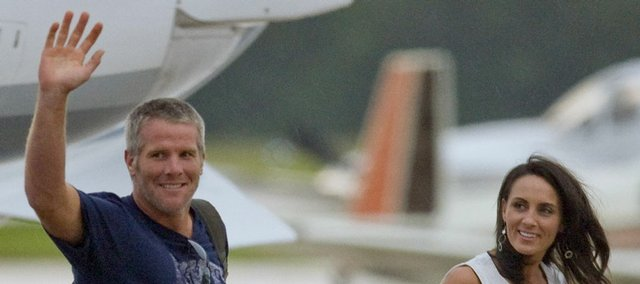 Brett Favre and his wife, Deanna, acknowledge fans as they get off a private jet Sunday at Austin Straubel International Airport in Green Bay, Wis.