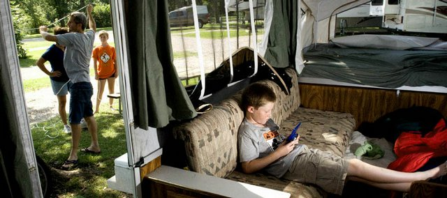 Ten-year-old Tanner Wendt, of Fox Lake, Ill., hides out in the family pop-up camper with a handheld computer game as his father, Greg, mother, Diane, and sister Taylor set up on the grounds outside at Lawrence Kampgrounds of America. According to KOA park manager Harold Hays, the campground is attracting more vacationers from communities closer to Lawrence such as Topeka and Kansas City because of the high cost of fuel.