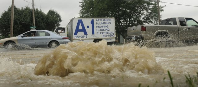 Motorists on Iowa Street pass a broken water main at Iowa Street and Yale Road on Wednesday morning. Traffic was restricted to one lane in each direction between Ninth Street and Harvard Road, and will remain that way until the road is completely repaired.