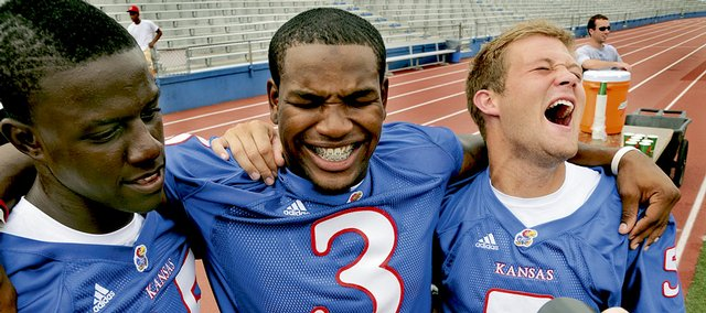 "Kansas University Football players, from left, Rod Harris Jr., Jocques Crawford and Todd Reesing laugh after freelance photographer Julie Daniel asked Crawford to ""show his grill"" for a photo. Tuesday's Media Day at Memorial Stadium and the Anderson Family Football Complex was the first meet-the-press event for Crawford, a ballyhooed running back. Incidentally, the ""grill"" comment referred to Crawford's braces."