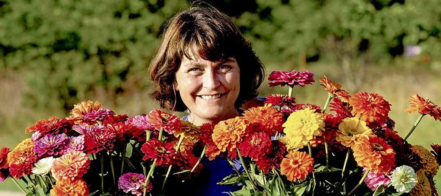 Lynn Byczynski is shown with bunches of zinnias she grows with her husband, Dan Nagengast, south of Lawrence. Byczynski and Nagengast sell their cut flowers to Porterfields Florist in Topeka.  They also sold to the Community Mercantile but have since taken on an even larger grocer, Ball Foods, which owns the Hen House chain.