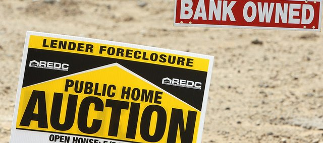 Signs like these are a common sight these days where auctions, bank-owned homes, foreclosures and unfinished housing developments dot the housing landscape like this home Wednesday in Phoenix. Freddie Mac on Wednesday posted a second-quarter loss more than three times larger than Wall Street expected as more homeowners fell behind on their mortgages.