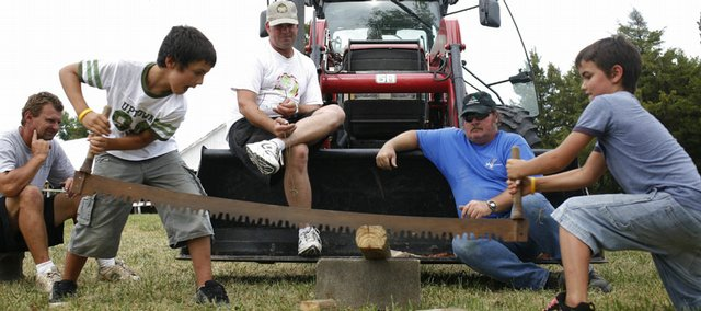 Simon Beach, 10, of Vinland, second from left, and Ian Beach, 9, of Vinland, team up to saw through a board Thursday during the Old-time Farm Skills Contest at the Vinland Fair. Fairgoers competed in basic farming skills like shelling corn, sawing and hay bale throwing. In the background from left iare Mark Brown, Mike Craig and Allen Osborn, all of Vinland.