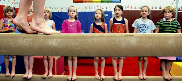 Students watch their instructor on the balance beam at a recent practice at the East Lawrence Parks and Recreation Center, 1245 E. 15th St.