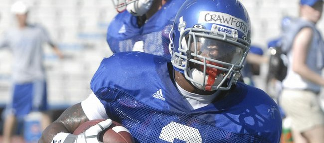 Kansas running back Jocques Crawford takes a handoff and looks for yardage. Crawford took reps with a first-team offense that looked explosive at the Jayhawks' open practice Friday at Memorial Stadium.